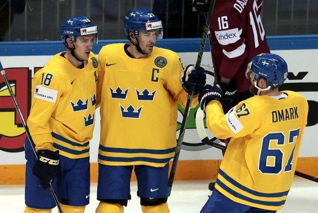 Jimmie Ericsson (uprostřed) se raduje z gólu se spoluhráči ze Švédska Mikaelem Backlundem (vlevo) a Linusem Omarkem.