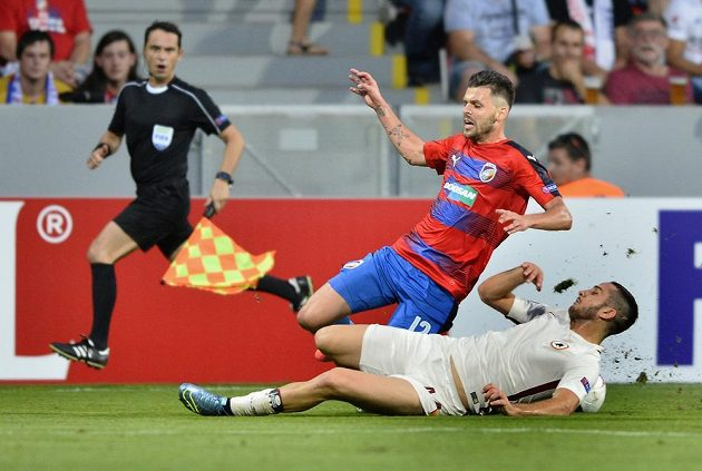 Michal Ďuriš z Viktorie Plzeň a Kostas Manolas z AS Řím (ležící) v tvrdém souboji o balón.