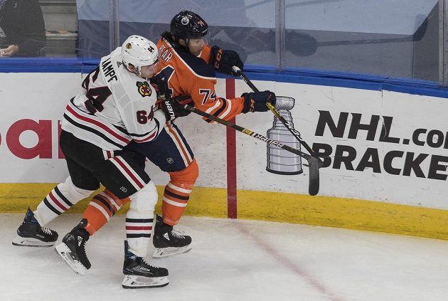 Ethan Bear (74) z Edmontonu Oilers čelí ataku Davida Kampfa z Chicaga Blackhawks.