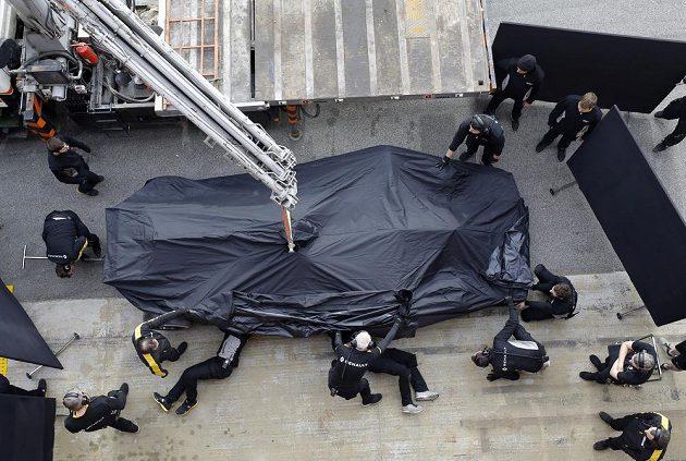 Mechanici Renaultu vykládají vůz z odtahového vozu po nehodě Jolyona Palmera.