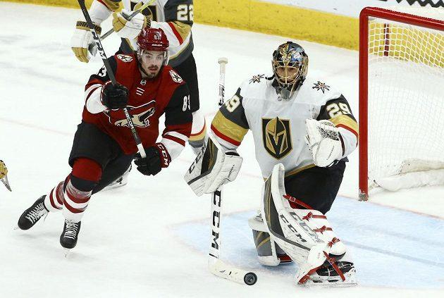 Brankář Las Vegas Marc-André Fleury je ve střehu před dotírajícím útočníkem Arizony Conorem Garlandem v zápase NHL.