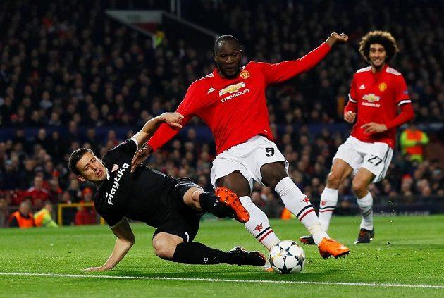 Stoper Sevilly Clement Lenglet vypichuje skluzem míč útočníkovi Manchesteru United Romelu Lukakovi.