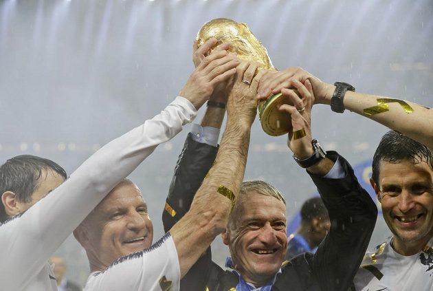 Trenér Francie Didier Deschamps zvedá pohár nad hlavu.