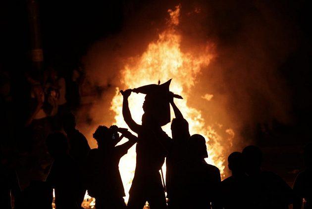 Demonstranti sledují zapálenou barikádu v Rio de Janeiru.