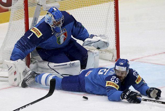 Brankář italské hokejové reprezentace Andreas Bernard a bránící Stefano Marchetti zastavují puk během utkání mistrovství světa s Lotyšskem.