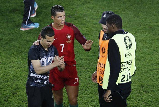 Cristiano Ronaldo domlouvá pořadatelům. S fanouškem, který vnikl na hrací plochu, se ochotně vyfotil.
