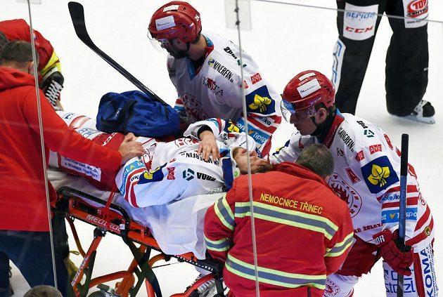 Zraněný třinecký útočník Ján Sykora opouští led na nosítkách.