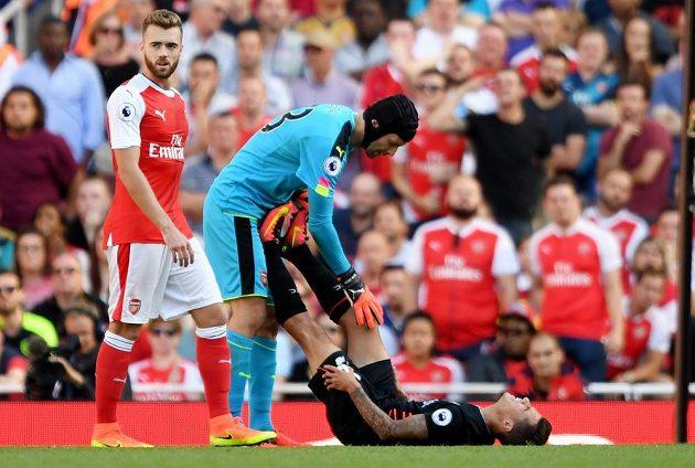 Liverpoolský Philippe Coutinho dostává pomoc od brankáře Arsenalu Petra Čecha, kolem něhož prochází spoluhráč Calum Chambers.