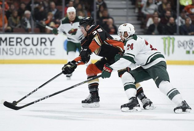 Český hokejista Anaheimu Ondřej Kaše (v černém) pod tlakem obránce Minnesoty Matta Dumby.