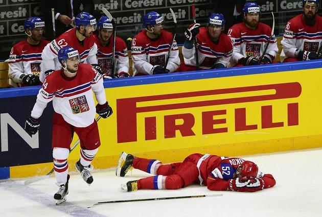 Rus Sergej Širokov leží před střídačkou českého týmu. Vlevo Tomáš Kundrátek.