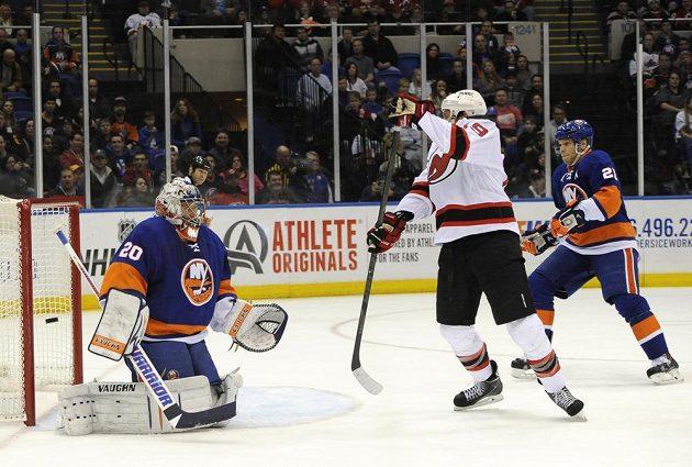 Puk se právě odrazil od krku Travise Zajace (uprostřed) z New Jersey za záda gólmana Islanders Jevgenije Nabokova.