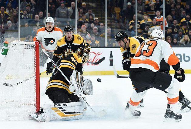 Brankář Bostonu Tuukka Rask (40) chytá puk v utkání NHL. Před ním sleduje situaci obránce Bruins Zdeno Chára (33), poblíž branky je i útočník Philadelphie Flyers Jakub Voráček (93).