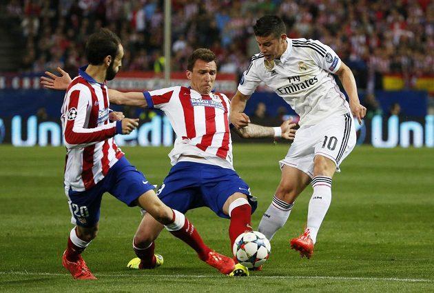 James Rodríguez z Realu se snaží prostřelit míč přes dvojici hráčů Atlétika Madrid - brání Juanfran a Mario Mandžukič (uprostřed).