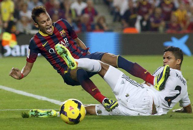 Útočník Barcelony Neymar v tvrdém souboji s Raphaelem Varanemk z Realu Madrid.
