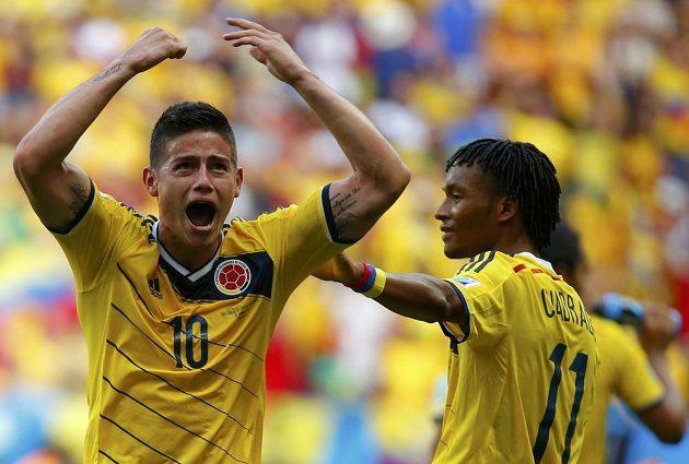 James Rodriguez (vlevo) jásá s dalším Kolumbijcem Juanem Cuadradem po vedoucí brance proti Pobřeží slonoviny.