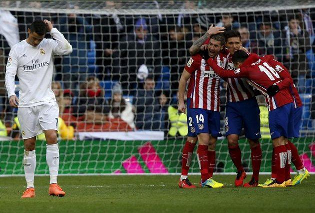 Cristiano Ronaldo z Realu a radující se hráči Atlétika po madridském derby.