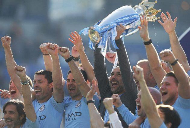Je to doma. Manchester City slaví mistrovský titul. S trofejí si užívá manažer Pep Guardiola s hráči.