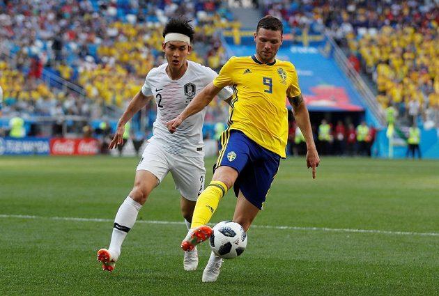 Švédský fotbalista Marcus Berg si kryje v utkání mistrovství světa míč před Korejcem Lee Jongem.