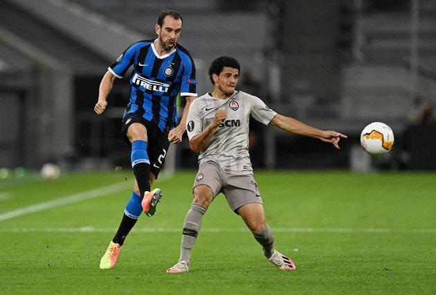 Obránce milánského Interu Diego Godín (vlevo) odkopává míč do bezpečí před Taisonem ze Šachtaru Doněck.