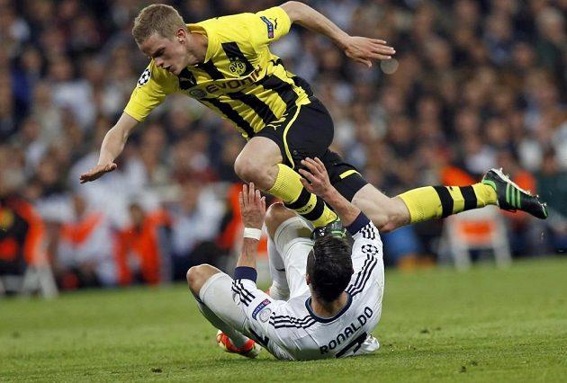 Dortmundský Sven Bender padá přes Cristiana Ronalda z Realu Madrid.