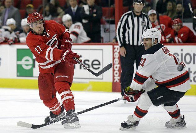 Stephen Gionta z New Jersey (vparvo) se snaží zablokovat střelu obránce Caroliny Justina Faulka v zápase NHL.