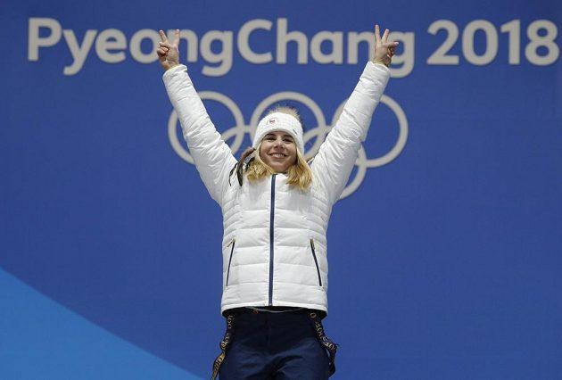Vítězné gesto zlaté medailistky Ester Ledecké při slavnostním ceremoniálu. Ledecká vyhrála senzačně super-G.