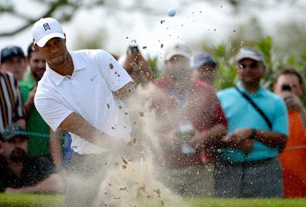 Tiger Woods odpaluje míček z pískového podkladu.