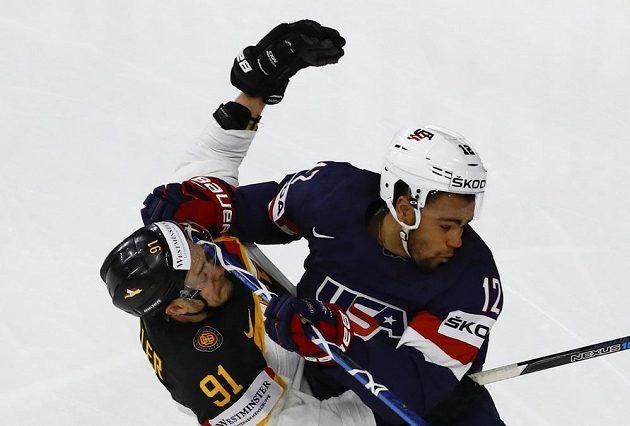 Ostrý souboj Jordana Greenwaye z USA a Moritze Müllera z Německa během utkání hokejového mistrovství světa.