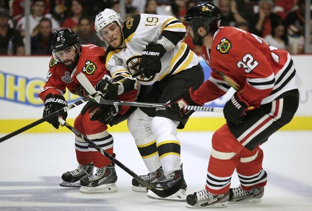 Útočník Bruins Tyler Seguin (uprostřed) v sevření chicagských zadáků Nicka Leddyho (vlevo) a Michala Rozsívala.