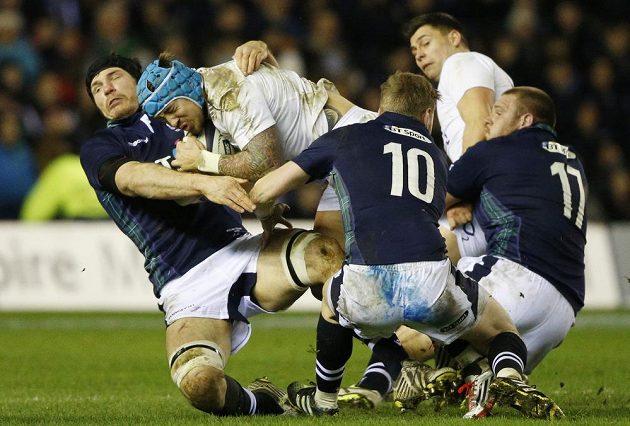 Angličan Jack Nowell se vrhá proti skotské zdi.