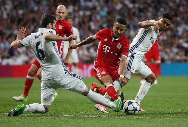 Thiago Álcantara z Bayernu se snaží projít přes bránící dvojici hráčů Realu Nacha (vlevo) a Casemira.