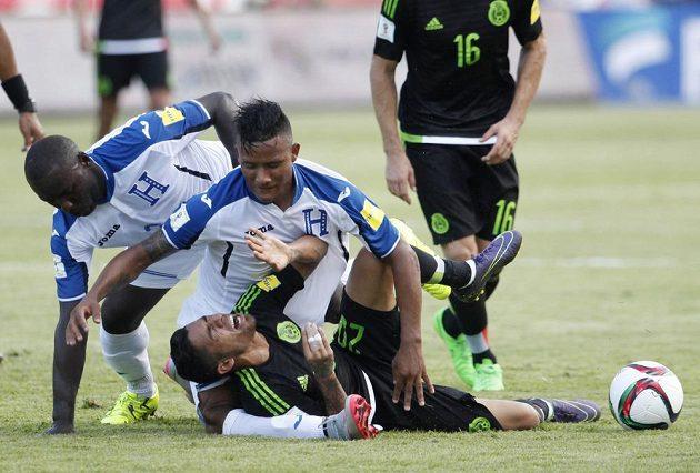 Fotbalista Hondurasu (uprostřed) Luis Garrido nešťastně nechal nohu pod padajícím Mexičanem Javiere Aquinem během kvalifikačního zápasu.