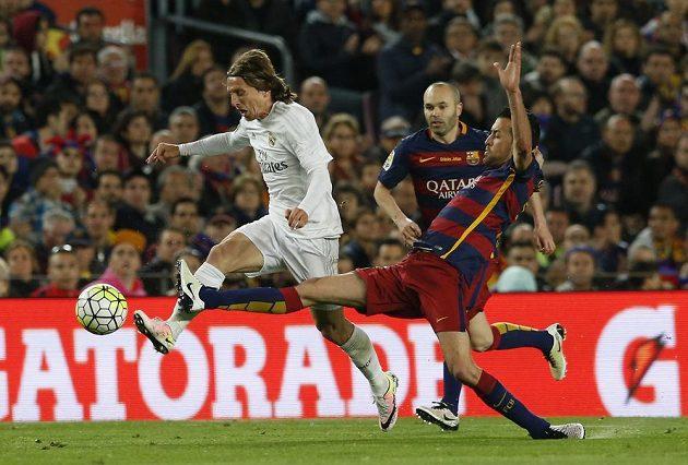Sergio Busquets z Barcelony se snaží ve slavném El Clásicu zastavit unikajícího Luku Modriče z Realu Madrid.