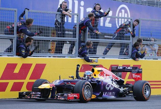 Sebastian Vettel projíždí cílem kolem jásajících mechaniků.