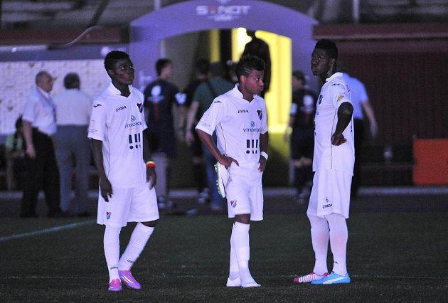 Zleva útočník Baníku Francis Narh a záložníci Derrick Mensah a Dyjan Carlos de Azevedo čekají na hrací ploše poté, co byla přerušena hra kvůli výpadku elektrického proudu.