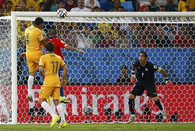 Australský útočník Tim Cahill (vlevo) střílí hlavou gól do sítě Chile. Vpravo je brankář Claudio Bravo.