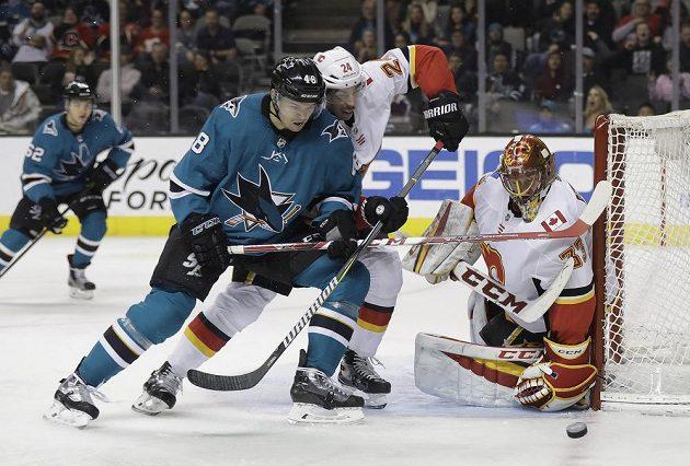 Útočník San Jose Tomáš Hertl se snaží v utkání NHL prosadit před brankou Calgary Flames. Vše sleduje český gólman Plamenů David Rittich.