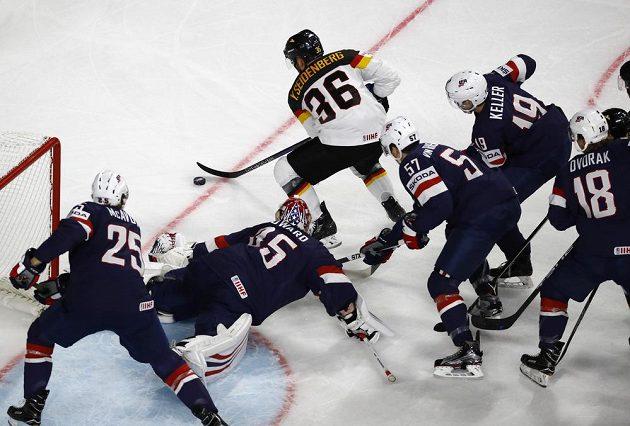 Německý hokejista Frederik Tiffels útočí. Před brankou USA čelí přesile soupeřů v čele s gólmanem Jimmy Howardem.