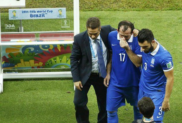 Zdrcený řecký fotbalista Theofanis Gekas (uprostřed) opouští stadión poté, co selhal v penaltovém rozstřelu.