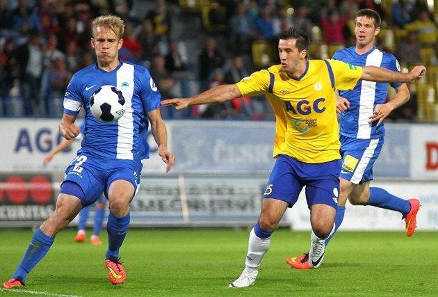 Teplický útočník Aidin Mahmutovič (ve žlutém dresu) se snaží dostat k míči přes libereckého obránce Lukáše Pokorného. Zcela vpravo přihlíží stoper Slovanu Jiří Pimpara.