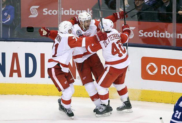 Dylan Larkin (71) a Henrik Zetterberg (40) objímají Jakuba Kindla (4) po jeho vítězné trefě v duelu proti Torontu Maple Leafs.