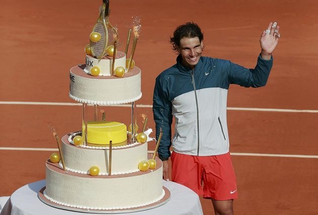 Španělský tenista Rafael Nadal stojící vedle svého narozeninového dortu zdraví fanoušky.