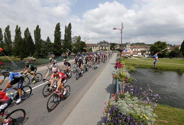 Cyklisté projíždějí přes kanál ve městě Baccarat během osmé etapy Tour de France.
