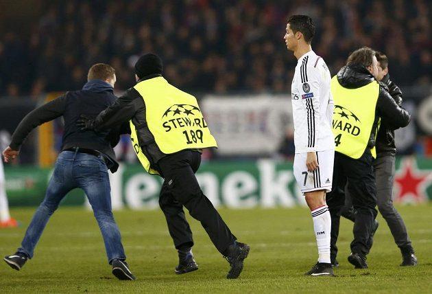 Cristiano Ronaldo z Realu přihlíží v Basileji počínání pořadatelů, kteří se snažili odchytit fanoušky na hrací ploše.