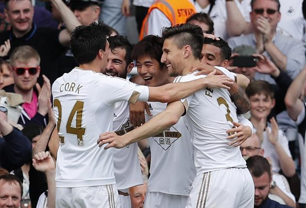 Ki Sung Yong ze Swansea slaví gól se svými spoluhráči do sítě West Hamu.