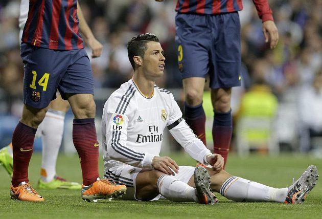 Na zemi sedící Cristiano Ronaldo z Realu Madrid v utkání s Barcelonou.