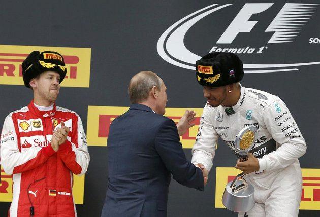 Lewis Hamilton přebírá cenu pro vítěze od ruského prezidenta Vladimira Putina. Vlevo přihlíží Sebastian Vettel z Ferrari.