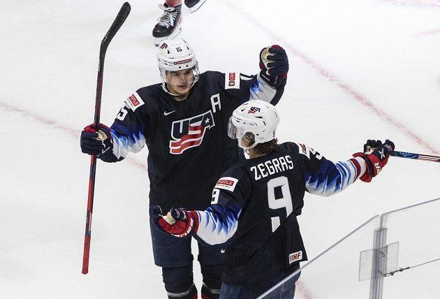 Američané Alex Turcotte (15) a Trevor Zegras (9) se radují z gólu proti Česku.