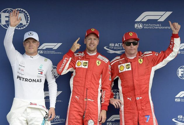 Vítěz sobotní kvalifikace na Velkou cenu Německa F1 Sebastian Vettel (uprostřed), druhý nejrychlejší čas zajel s monopostem Mercedes finský závodník Valtteri Bottas a na pomyslný bronz dosáhl v kvalifikaci s Ferrari další Fin Kimi Raikkönen