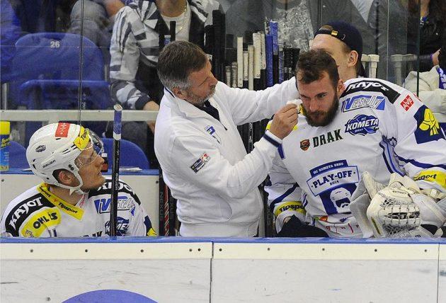Brněnský brankář Marek Čiliak si nechává ošetřit zranění od puku vystřeleného mimo led.